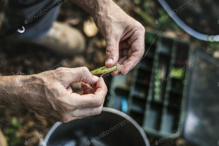 Closeup of a fisherman putting on bait
