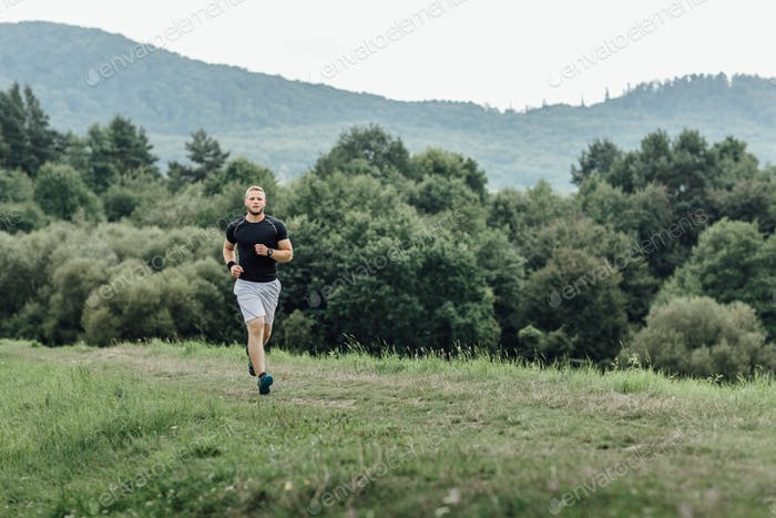 Male runner running along a nature trail across the country