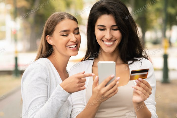 Weibliche Freunde halten Kreditkarte und mobile Anwendung