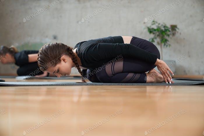 Fit Frau üben Kind Pose in der Halle