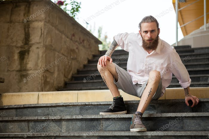 Cool tattoed and bearded guy posing outdoor