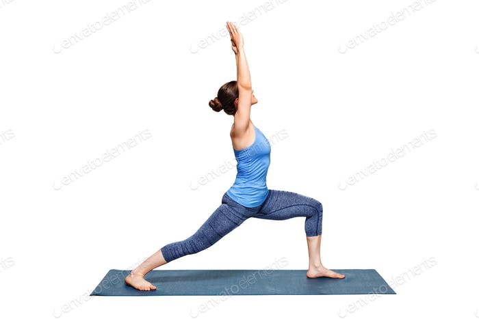 Sporty fit woman practices yoga asana utthita Virabhadras