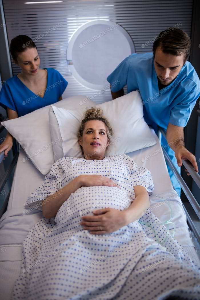 Team of doctors taking pregnant woman to operation theatre