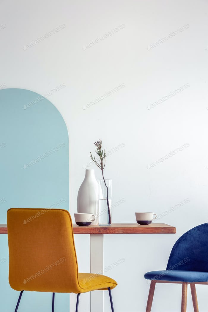 Weiße Vase auf Holztisch mit ausgefallenem Esszimmer Interieur mit weißen und blauen Wand