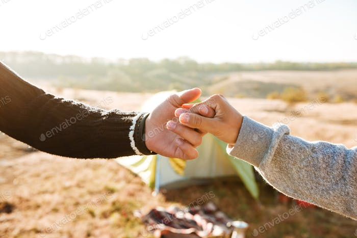 Couple holding hands near the tent