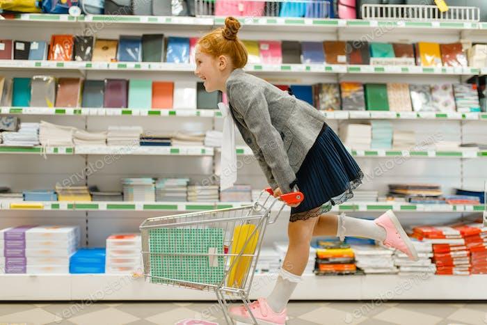 Schulmädchen mit Warenkorb, Einkaufen im Schreibwarengeschäft