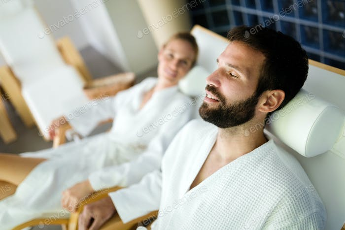 Attractive happy couple relaxing in spa center
