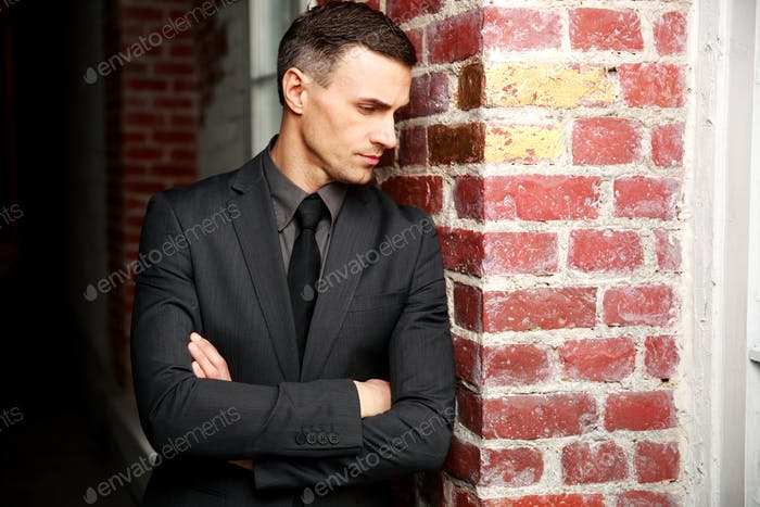 Pensive businessman standing with arms folded near brick wall