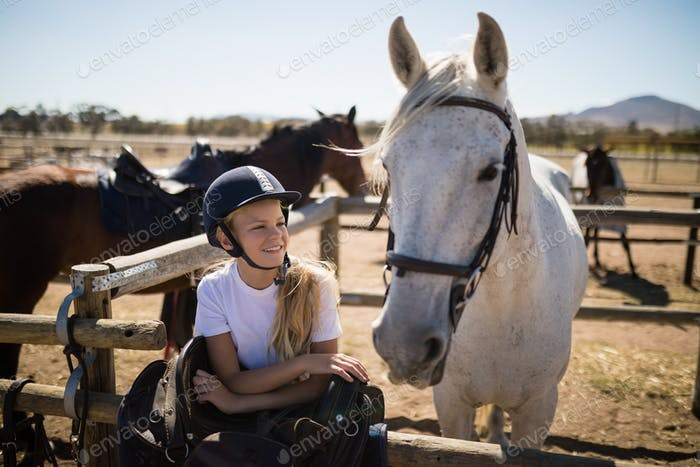 Smiling girl leaning on the fence and looking at the white horse in ranch