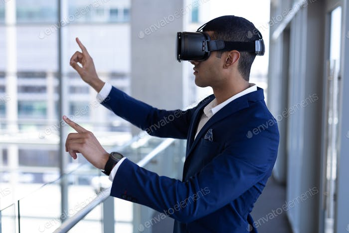 Businessman using virtual reality headset standing in modern office