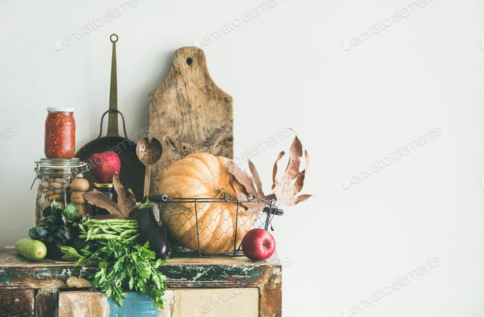 Autumn food ingredients and utensils over wooden cupboard, copy space