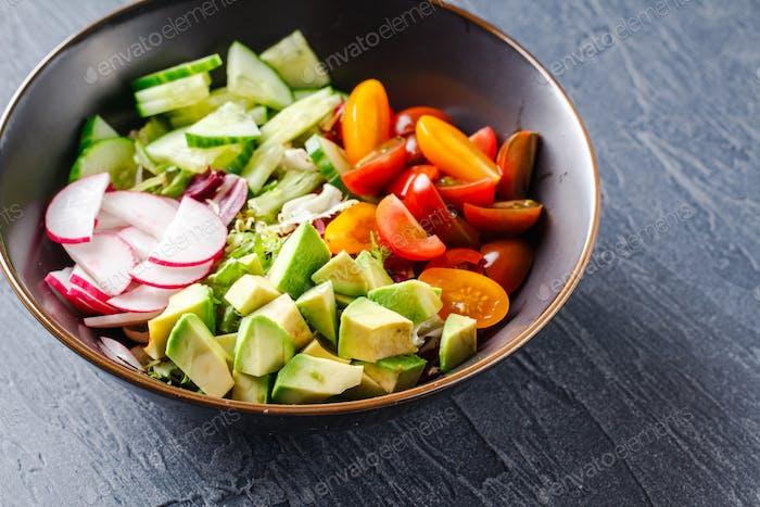 Vegan buddha bowl. Healthy vegetarian salad with cherry tomatoes, cucumber, radish, avocado, lettuce