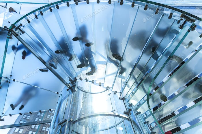 Low angle view of people walking on transparent spiral staircase.