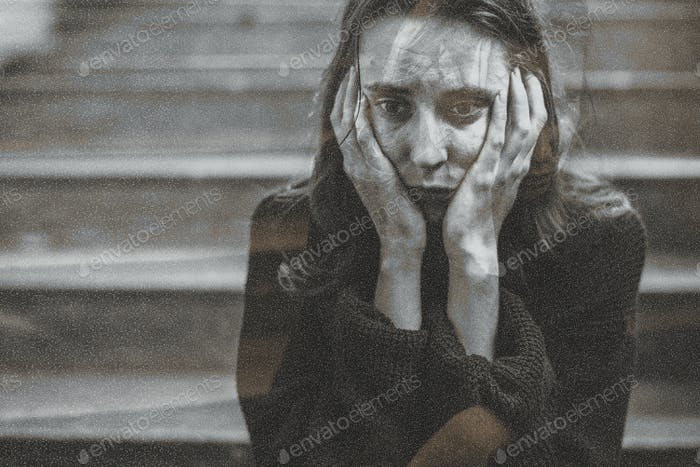 Distressed woman sitting on a staircase thinking deeply