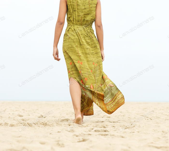 Portrait of a woman walking barefoot at the beach