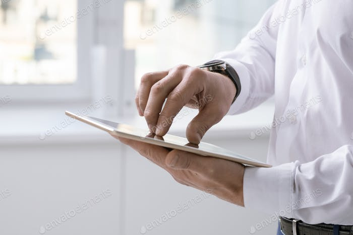 Hands of businessman with digital tablet over touchscreen preparing presentation