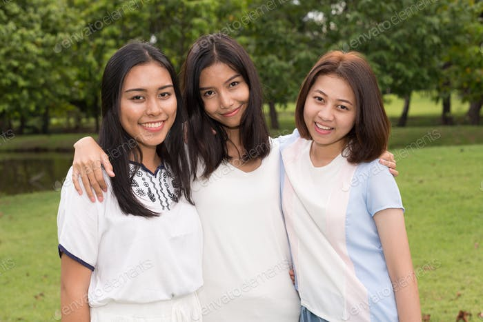 Portrait of three young beautiful Asian teenage girls as friends together at the park