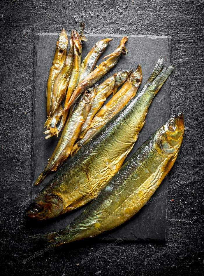 Different smoked fish on a stone Board.
