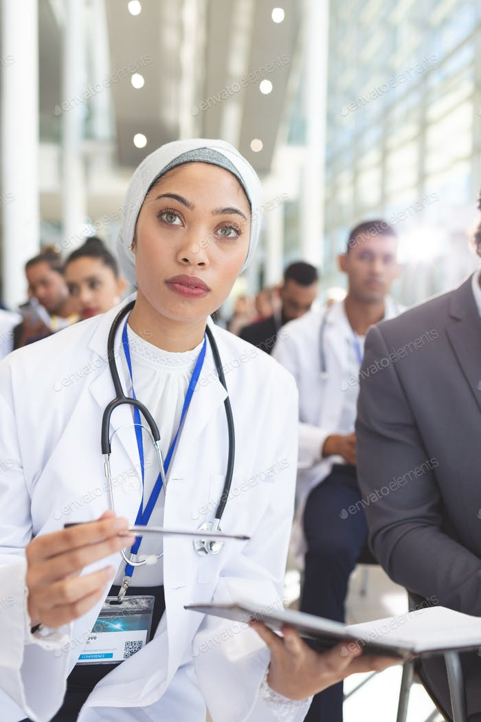 Front view of mixed race  female doctor with notebook and pen attending seminar in conference room