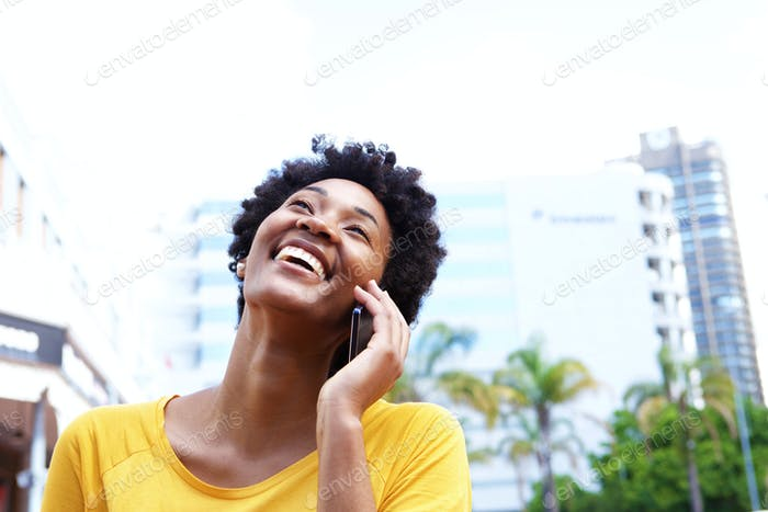 Cheerful young woman talking on mobile phone in the city