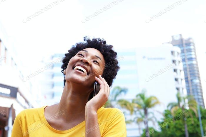 Fröhliche junge Frau im Gespräch auf dem Handy in der Stadt