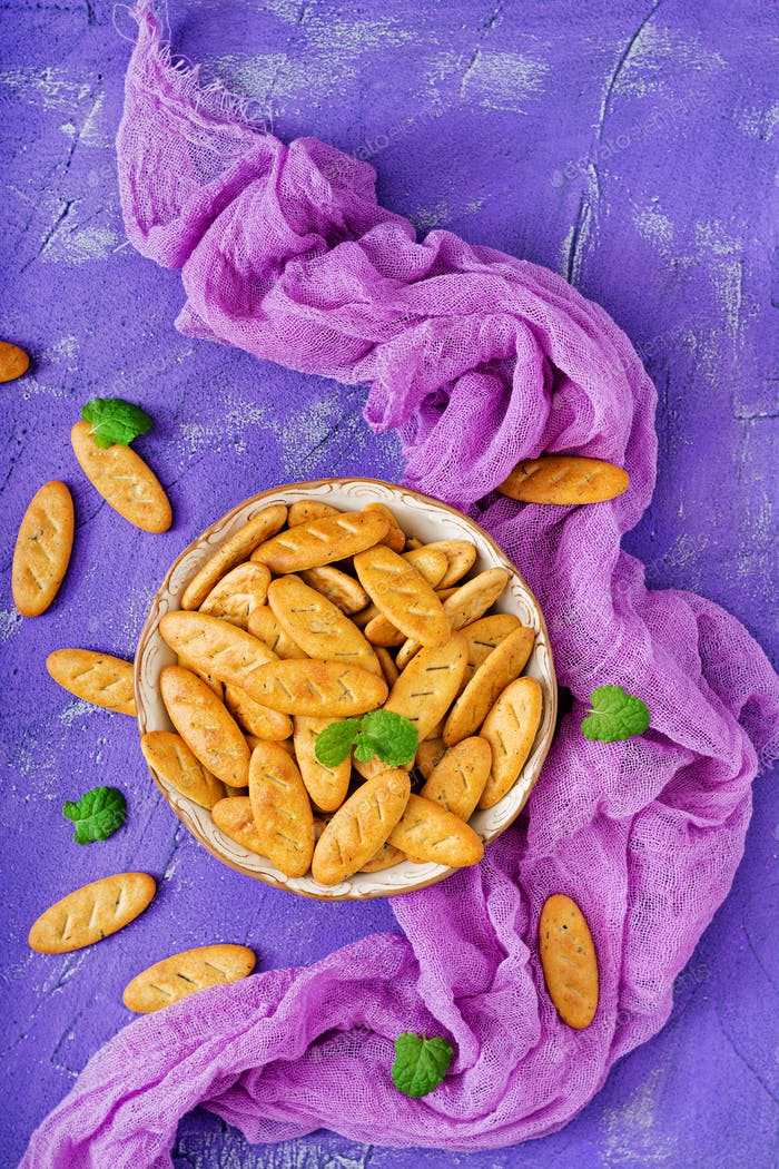 Cookies in a bowl on a purple background. Flat lay. Top view