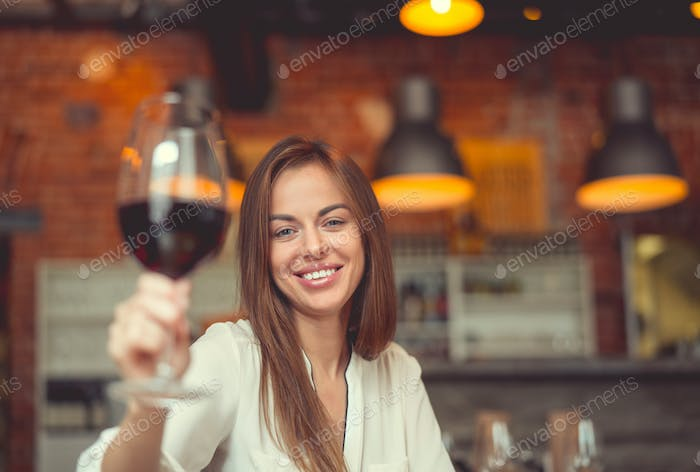 Young smiling girl with a glass of wine