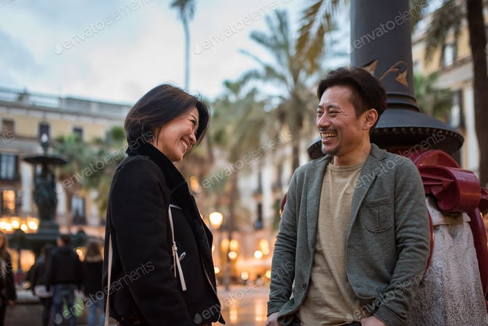 Asian happy tourist couple talking in a square