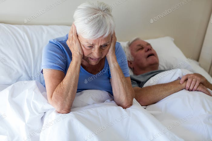Senior woman getting disturbed with man snoring on bed
