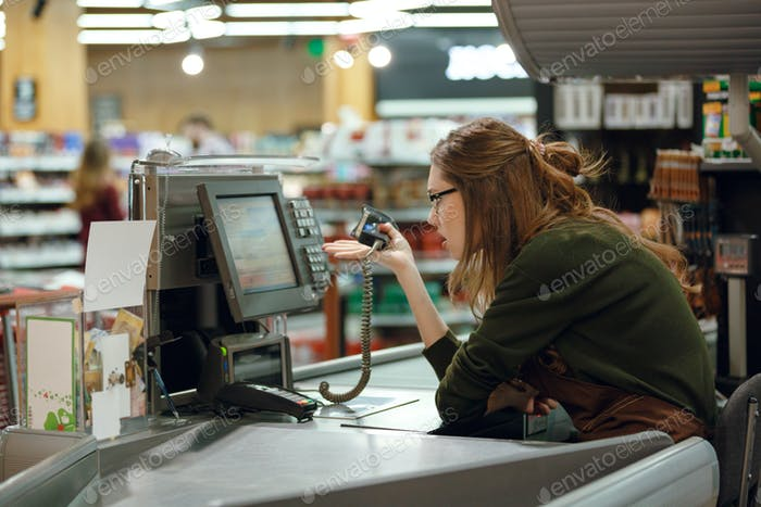 Confused cashier on workspace in supermarket shop.