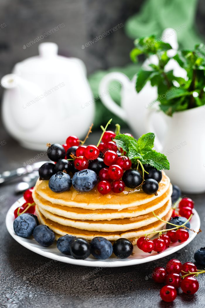 Pancakes with fresh berries. Pancakes with raspberry, blueberry, redcurrant, black currant and honey