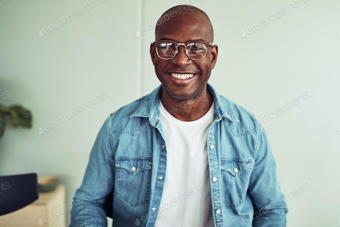 Lächelnd junge afrikanische Geschäftsmann sitzt in einem modernen Büro