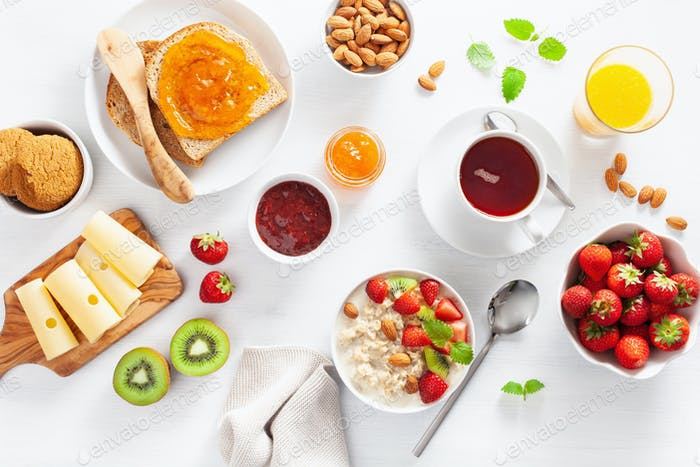healthy breakfast with oatmeal porridge, strawberry, nuts, toast