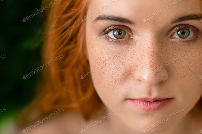 Beautiful young freckled green-eyed lady with red hair