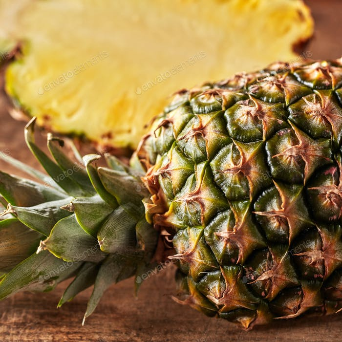 Closeup of whole and half juicy healthy pineapple presented on a kitchen board on a wooden table