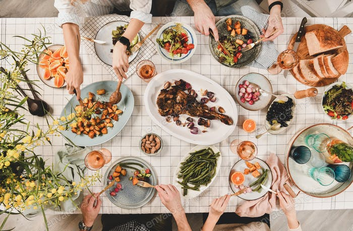 Peoples hands over table with meat, salads, rose wine