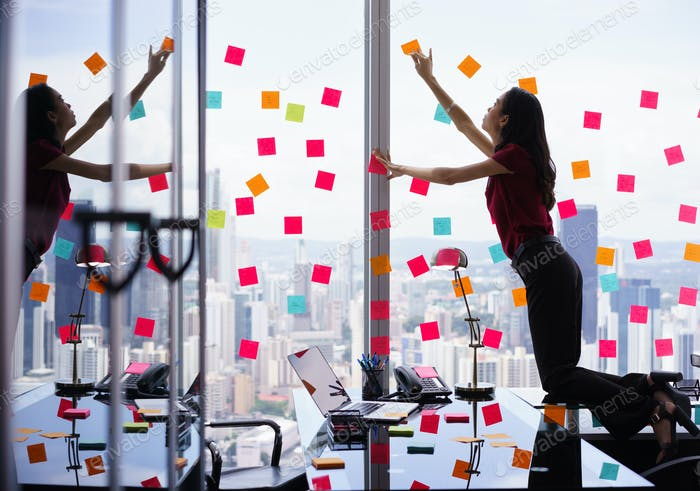 Busy Person Attaching Many Sticky Notes On Large Window