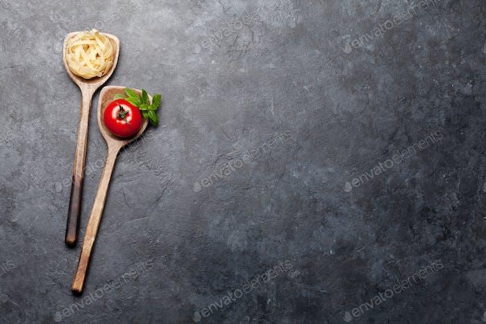 Pasta und Zutaten in Löffeln