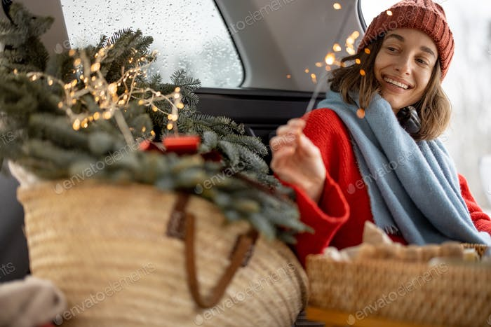 Woman smiling and looking at sparkler while sitting in car trunk