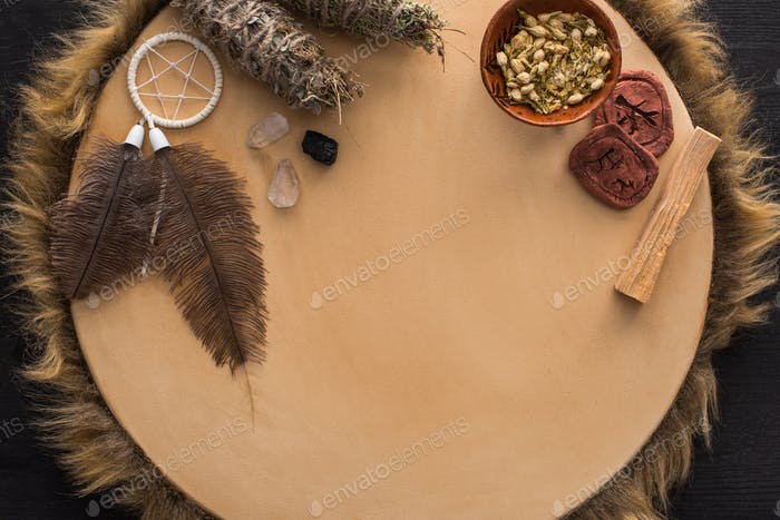 Smudge Sticks With Dry Flowers, Dreamcatcher And Clay Amulets on Tambourine on Dark Wooden Surface