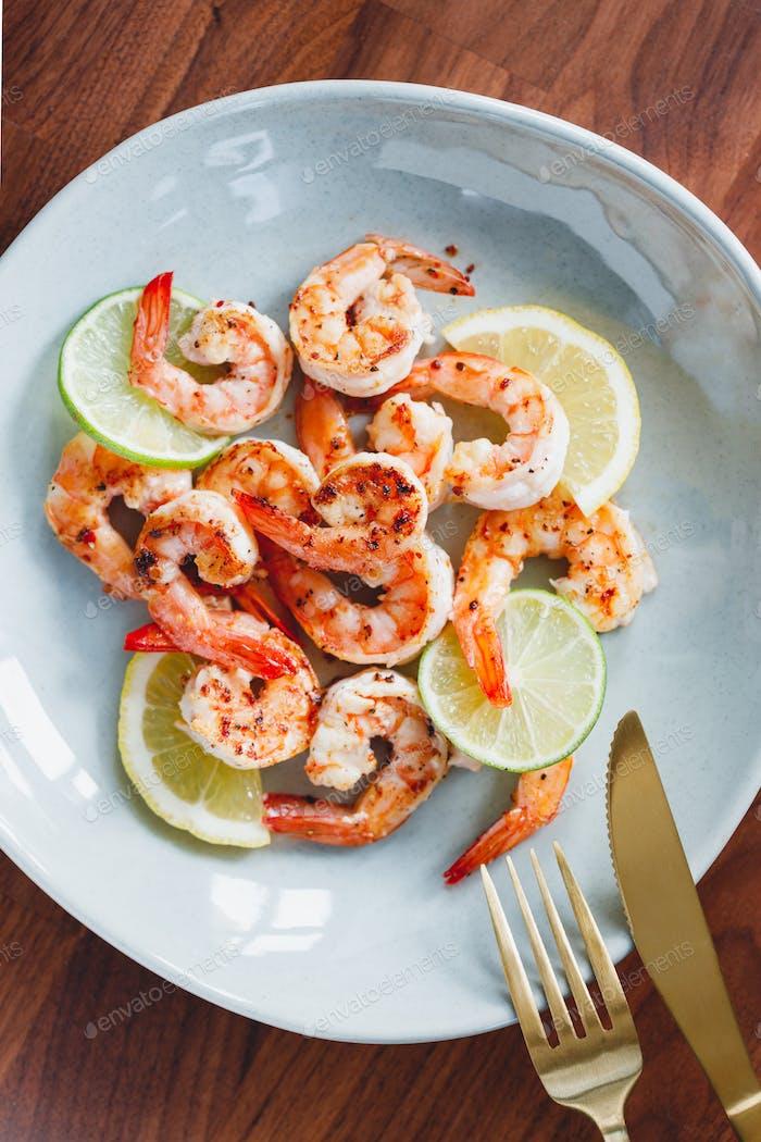 Gebratene Tigergarnelen mit Limette, Zitrone und Gewürzen auf einer Keramikschale. Gesundes Abendessen oder Mittagessen Konzept.
