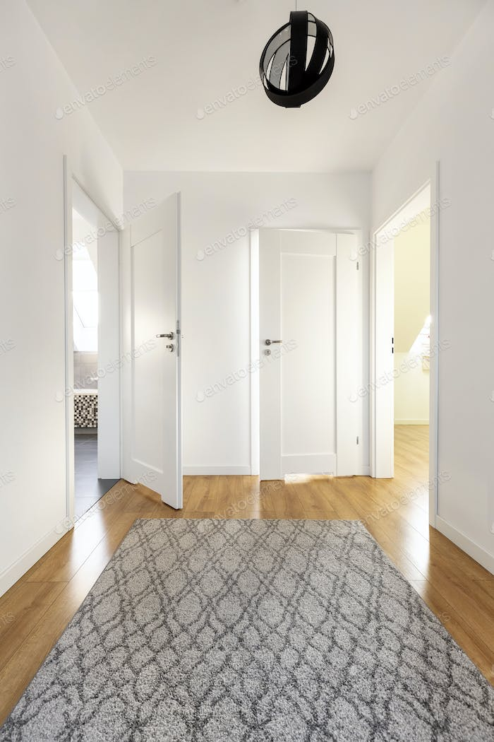 Real photo of a wide corridor with gray rug on the wooden floor