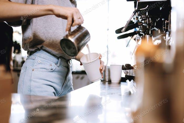 Ein jugendliches dünnes blondes Mädchen, das lässig Cothes trägt, wird gezeigt, Milch zum Kaffee in einem gemütlichen