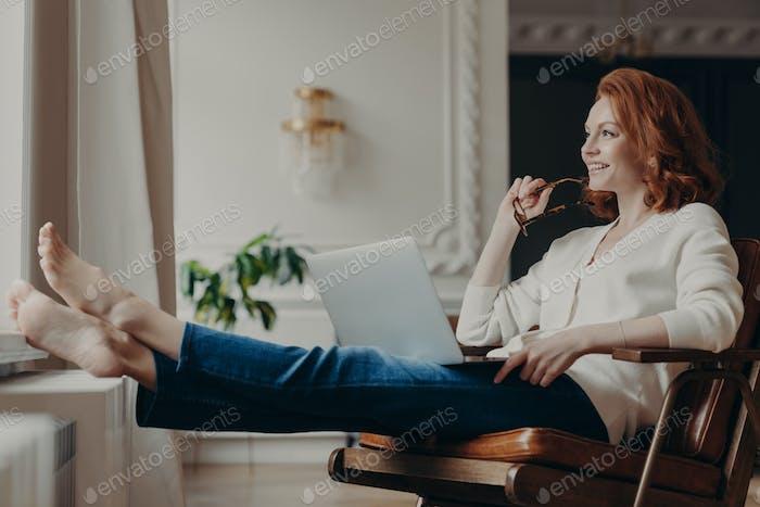 Nachdenklich zufriedene Freiberuflerin arbeitet zu Hause mit dem Computer