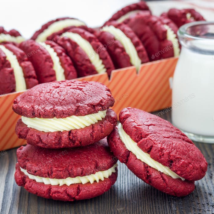 Red velvet sandwich cookies with cream cheese filling on wooden table, square