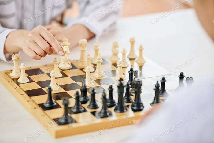 People playing chess game at table