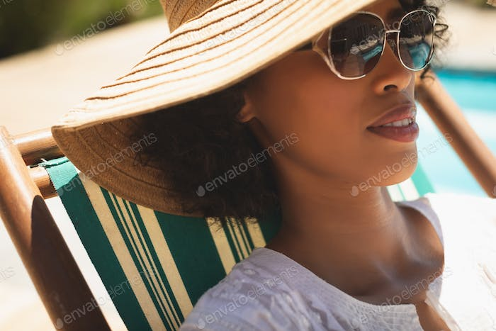 Beautiful young woman on vacation with hat and sunglasses relaxing on sun lounger on a sunny day