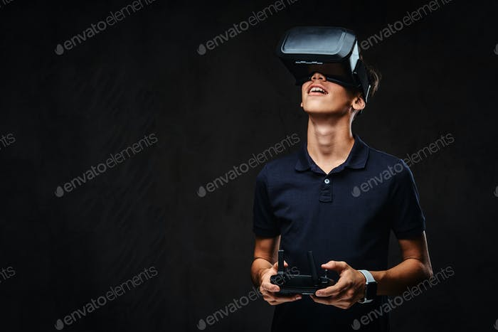 Junge Teenager in einem schwarzen T-Shirt gekleidet trägt Virtual-Reality-Brille und hält einen Quadcopter