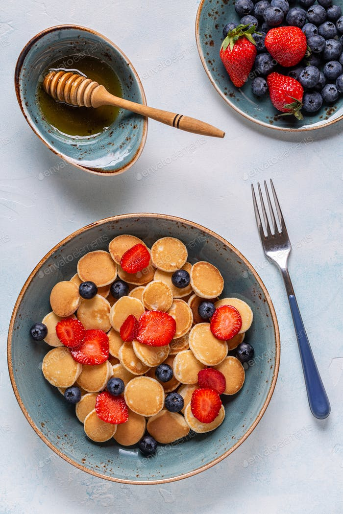 Trendy breakfast with mini pancakes, blueberries and strawberries