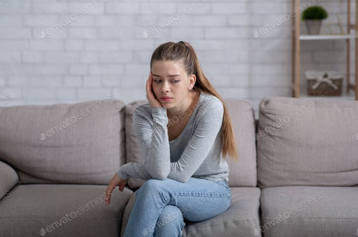 Mental health concept. Young woman having depression on sofa at home
